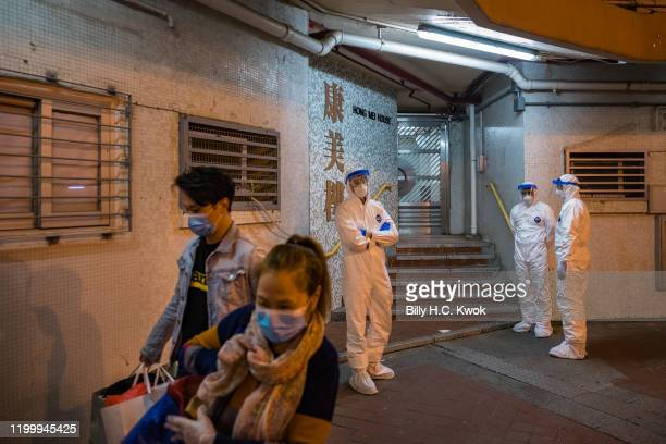 Residents leaving Hong Mei House as officials wearing protective gear stand guard outside an entrance at Cheung Hong Estate in the Tsing Yi district...