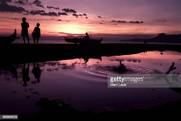 Residents leisurely stroll down the beach on February 1, 2001 in Maladeg, Philippines. Most of the land in the coastal village Maladeg was owned by...