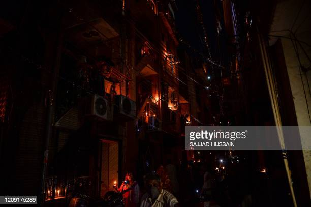 Residents light candles and turn on their mobile phone lights on their balconies to observe a nine-minute vigil called by India's Prime Minister in a...