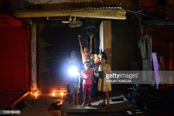 Residents light candles and turn on their mobile phone lights outside their home to observe a nine-minute vigil called by India's Prime Minister in a...