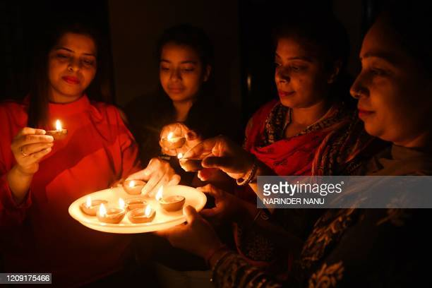Residents light diyas or oil lamps outside their home to observe a nineminute vigil called by India's Prime Minister in a show of unity and...