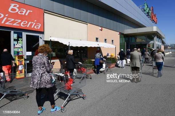 Residents line up at a safety distance as they wait to shop at a supermarket in Codogno southeast of Milan on March 11 2020 a day after Italy imposed...
