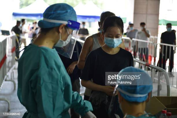 Residents line up at a sampling area for nucleic acid testing in Nanjing, East China's Jiangsu Province, Aug. 6, 2021. The WORLD Health Organization...