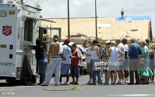 Residents line up for donated goods from a Salvation Army truck in front of a damaged church August 16, 2004 in Port Charlotte, Florida. Hurricane...