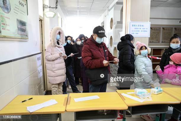 Residents line up to be tested for the COVID-19 coronavirus in Shenyang, in China's northeast Liaoning province on December 31, 2020. / China OUT