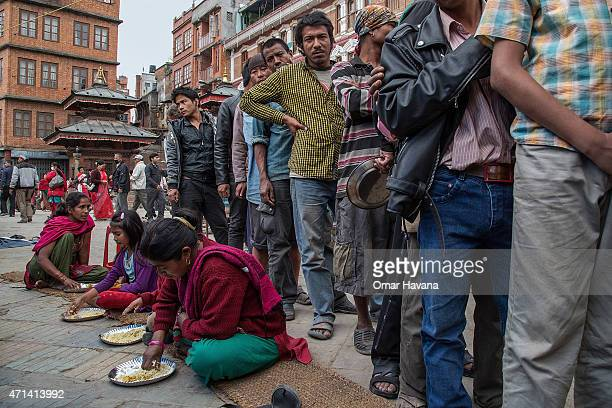 Residents line up to get food at one of the temporary street shelters near Basantapur Durbar Square on April 28, 2015 in Kathmandu, Nepal. A major...