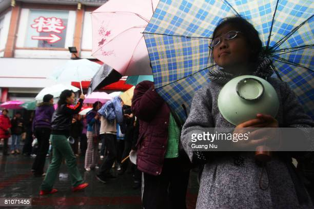 Residents line up to get free food following the earthquake May 13 2008 in Sichuan province Dujiangyan City China A major earthquake measuring 78 on...