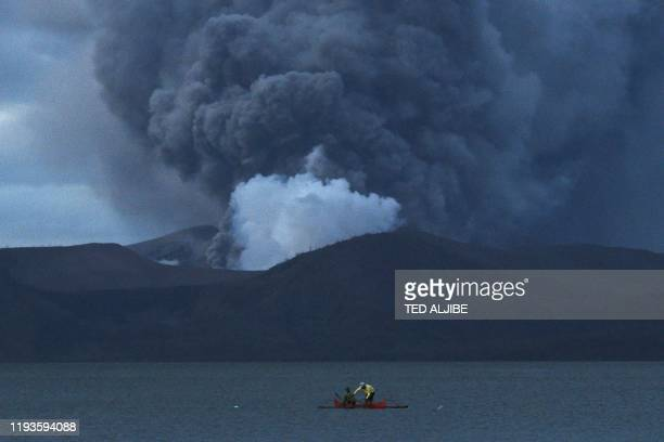 TOPSHOT Residents living along Taal lake catch fish as Taal volcano erupts in Tanauan town Batangas province south of Manila on January 14 2020 Taal...