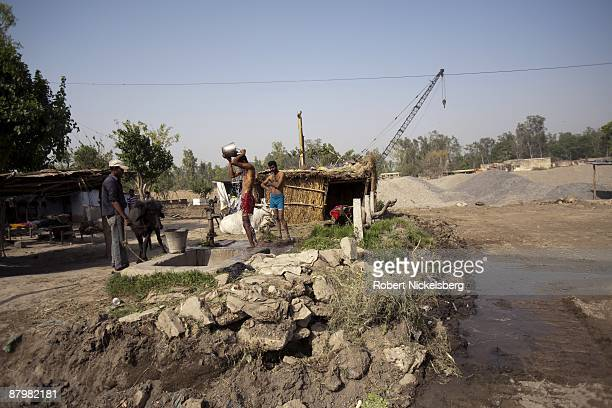 Residents living in a disappearing slum take baths as a bulldozer grades land in front of their homes near a newly dug roadway April 23 2009 where...