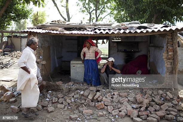 Residents living in a slum area gather bricks to relocate their home near a newly dug roadway April 23 2009 where agricultural areas they and members...