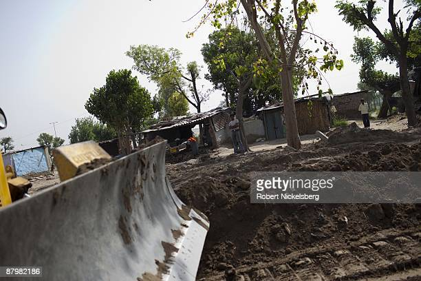 Residents living in a slum area watch as a bulldozer grades land in front of their homes near a newly dug roadway April 23 2009 where agricultural...