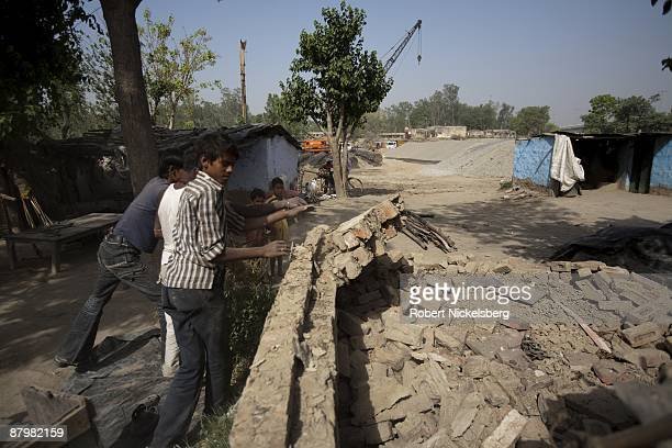 Residents living in a slum push down a wall of bricks to relocate their home April 23 2009 where agricultural areas they and members of twelve...