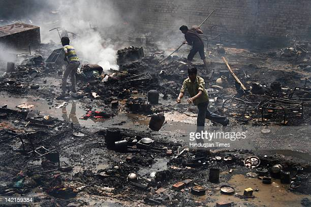 Residents look after a fire incident at Navada village, Sector-62 on March 31, 2012 in Noida, India. Reportedly, two children lost their lives in the...