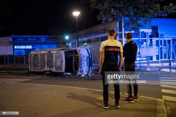 Residents look at a burnt car in the Breil neighborhood of Nantes early on July 4 2018 Groups of young people clashed with police in the western...