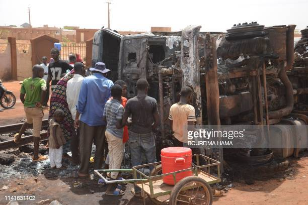 Residents look at a calcined tanker truck after an explosion which killed more than 55 people near the airport of Niamey on May 6 2019 Fiftyfive...