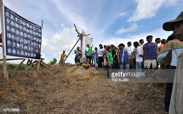Residents look at a collage of the victims of the November 23 2009 massacre posted at the site in Ampatuan Maguindanao province in southern island of...