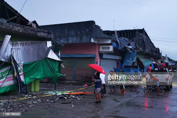 Residents look at a destroyed building after a 6.8- magnitude earthquake in the town of Padada in Davao del Sur province on the southern island of...