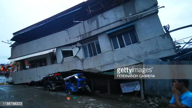 TOPSHOT Residents look at a destroyed house with a vehicle squeezed underneath after a 68 magnitude earthquake in the town of Padada in Davao del Sur...