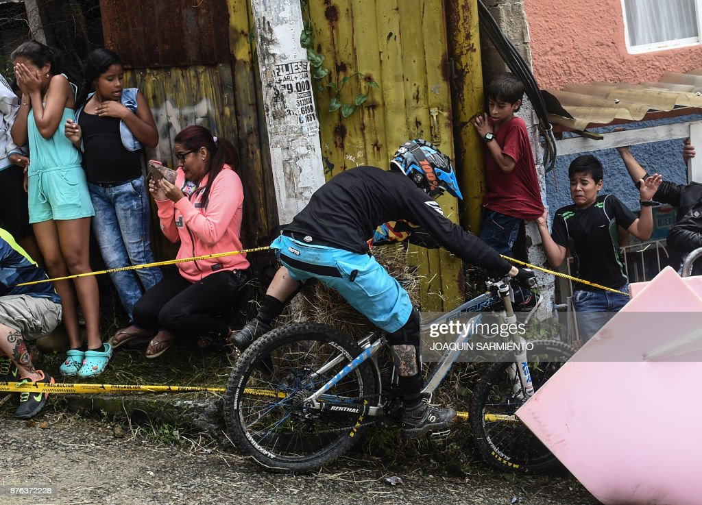 Residents look at a downhill rider crashing during the Urban Bike Inder Medellin race final at the Comuna 1 shantytown in Medellin, Antioquia department, Colombia on November 19, 2017. /