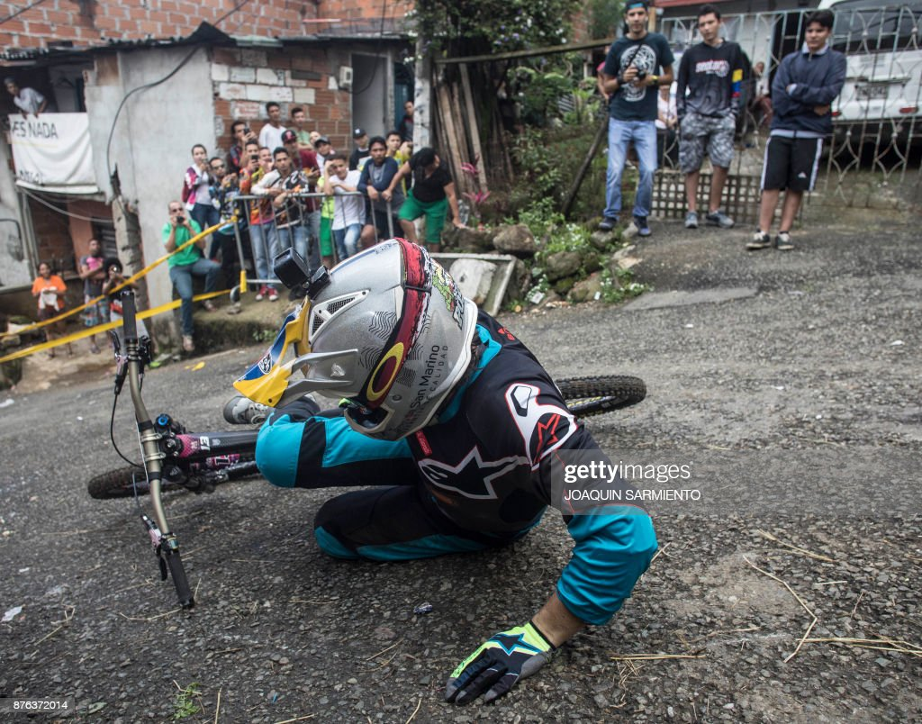 Residents look at a downhill rider during the Urban Bike Inder Medellin race final at the Comuna 1 shantytown in Medellin, Antioquia department, Colombia on November 19, 2017. /