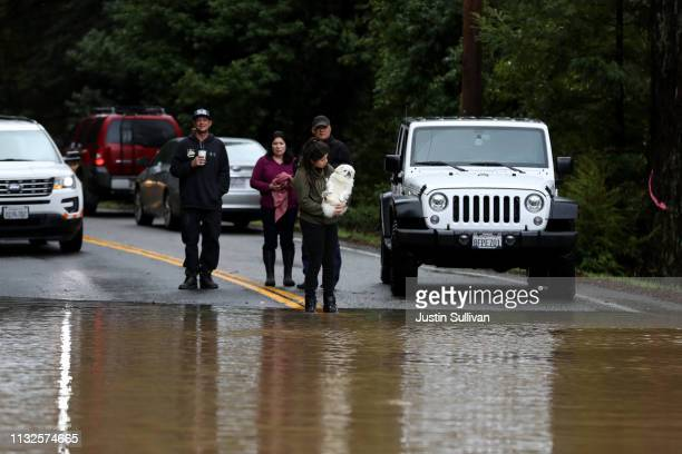 Residents look at a flooded section of highway 116 on February 27 2019 in Guerneville California The Russian River has crested over flood stage and...