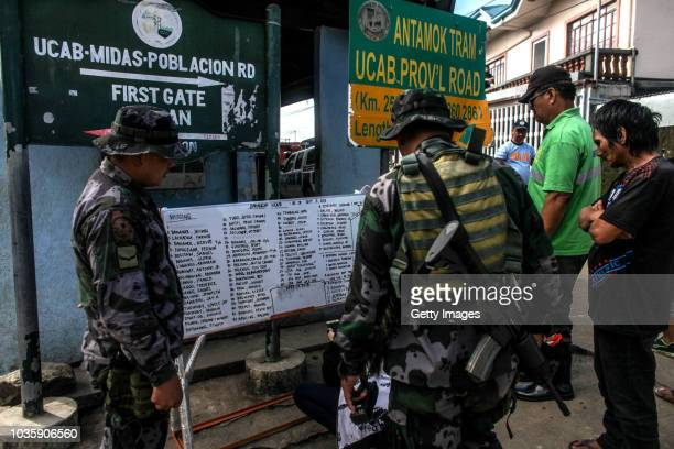 Residents look at a list of names of victims killed by a landslide on September 19 2018 in Itogon Benguet province Philippines Dozens of people are...
