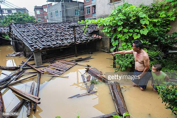 TOPSHOT Residents look at an inundated house as they stand in floodwaters in Putian in eastern China's Fujian province on July 9 2016 A tropical...