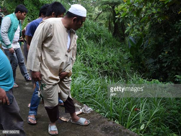 Residents look at bodies dumped off a cliff along the highway leading to Marawi on thesouthern island of Mindanao on May 28 2017 Islamist militants...
