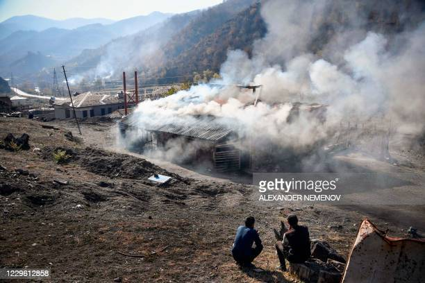 Residents look at burning houses in the village of Charektar outside the town of Kalbajar on November 14 during the military conflict between Armenia...