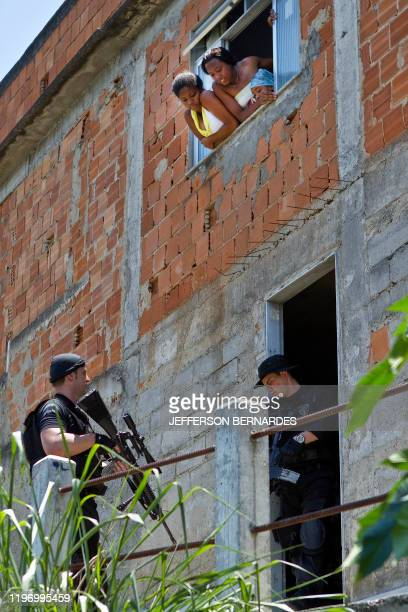 Residents look at Coordination of Special Resources policemen as they patrol Morro do Alemao shantytown on November 29 2010 in Rio de Janeiro Brazil...