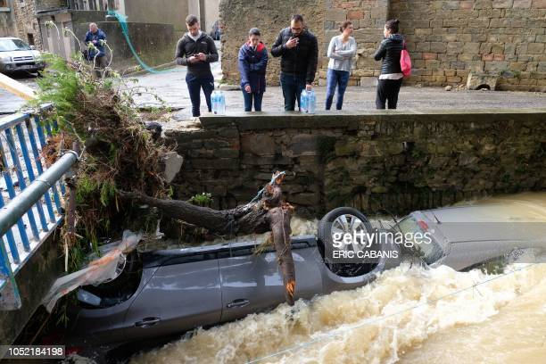 TOPSHOT Residents look at damaged cars on the Trapel river following heavy rains that saw rivers bursting banks on October 15 2018 in Villegailhenc...