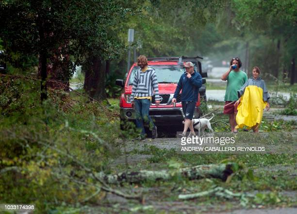 Residents look at downed tree as Hurricane Florence passes over Wilmington North Carolina on September 14 2018 Florence smashed into the US East...