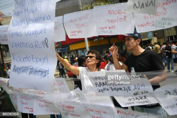 TOPSHOT Residents look at papers with the names of perons who went missing since the 71magnitude quake on the eve in Mexico City on September 20 2019...