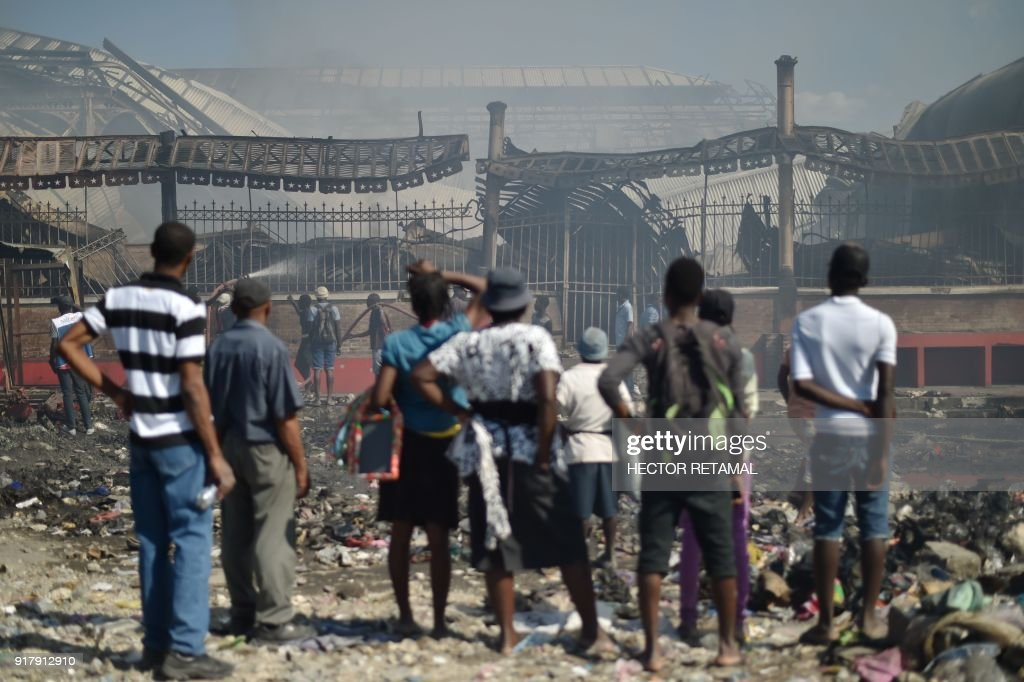 TOPSHOT - Residents look at the aftermath of a fire which destroyed the Iron Market in Port-au-Prince on February 13, 2018. Fire ravaged a historic market leaving burned-out merchants fearing for their livelihoods in the impoverished nation.The Iron Market was rebuilt in 2011 after the 2010 Haiti eartquake. There were no immediate reports of casualties nor the cause of the fire. /