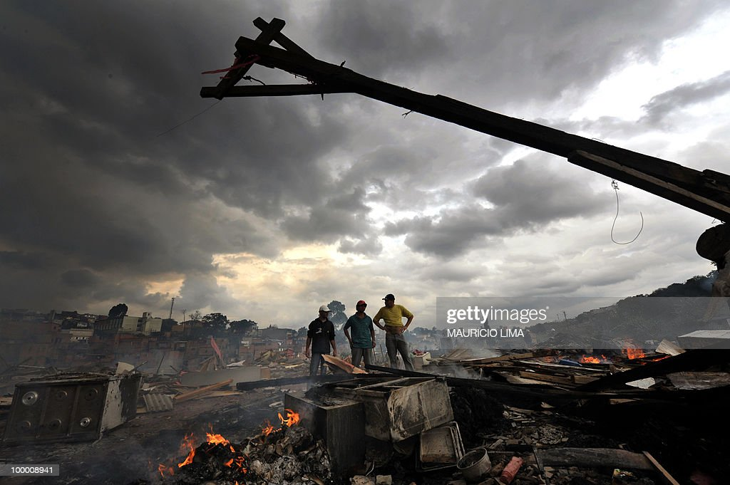 Residents look at the rubble during an eviction at Capao Redondo shantytown, southern outskirts of Sao Paulo, Brazil, on August 24, 2009. Residents set huts on fire as a way to protest. Almost 800 families (some 1200 people) were removed from their huts in a huge area which was illegaly occupied by them since 2007. AFP PHOTO/Mauricio LIMA