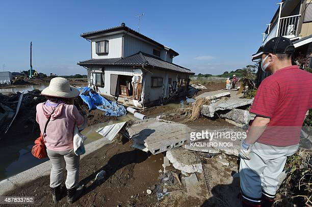 Residents look at their collapsed house near the burst point of the Kinugawa river in Joso city Ibaraki prefecture on September 12 2015 Japanese...