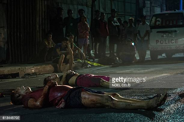 Residents look at two dead bodies lying on the road after they were gunned down by unidentified men riding a motorcycle in Manila on October 3 2016...