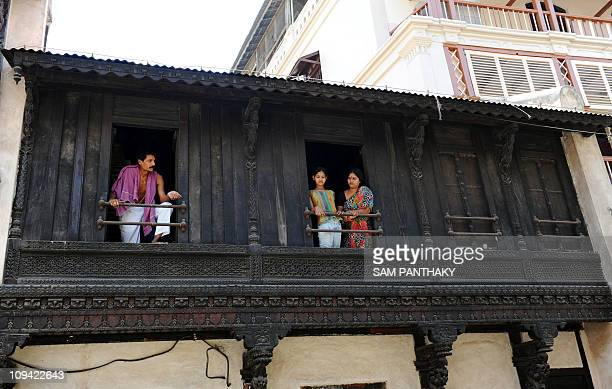 Residents look down from a carved wooden balcony in the walled city surrounding the Hatkeshwar Mahadev temple in Ahmedabad on April 17 eve of World...