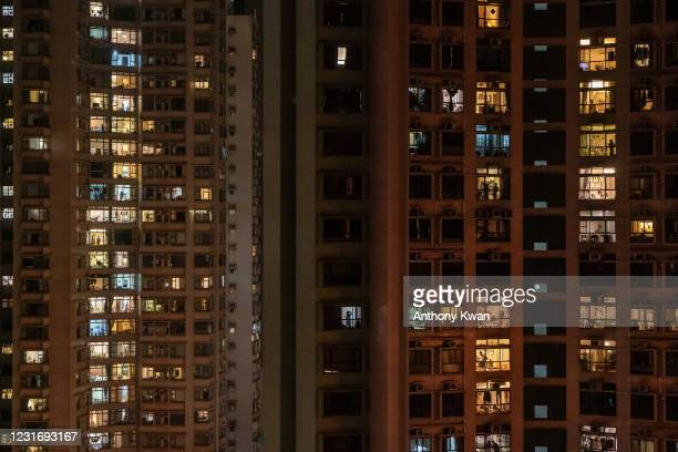 Residents look down from buildings in an area under lockdown on Robinson Road at night in the mid-Levels neighborhood on March 13, 2021 in Hong Kong,...