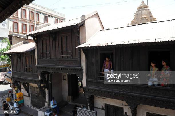Residents look down from the windows of a carved wooden house in the walled city surrounding the Hatkeshwar Mahadev temple in Ahmedabad on April 17...