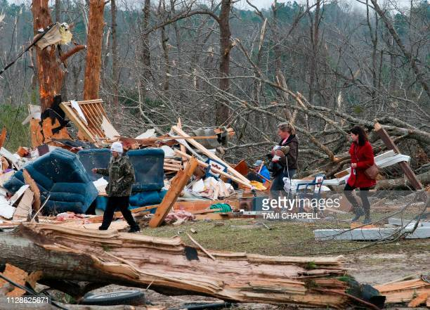TOPSHOT Residents look for belongings March 4 2019 at a home after it was destroyed in a tornado in Beauregard Alabama Rescuers in Alabama resumed...