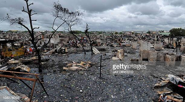 Residents look for salvageable materials in the debris after a fire gutted a sprawling shanty town in Malabon part of Metro Manila shortly before...