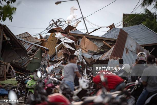 TOPSHOT Residents look for their belongings amid the debris of destroyed houses in Palu in Central Sulawesi on September 29 after a strong earthquake...