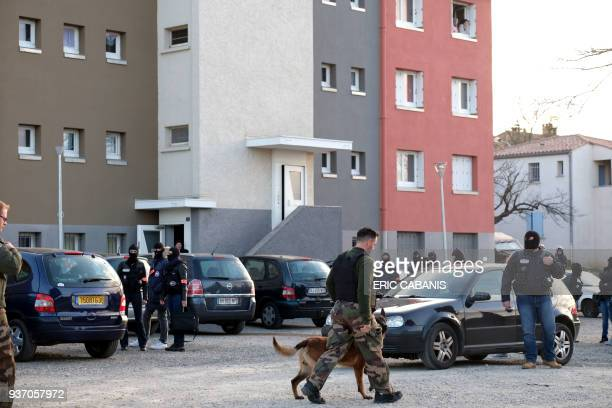 Residents look from the window as a member of the French Research and Intervention Brigade secures the area during a search operation at the Ozanam...