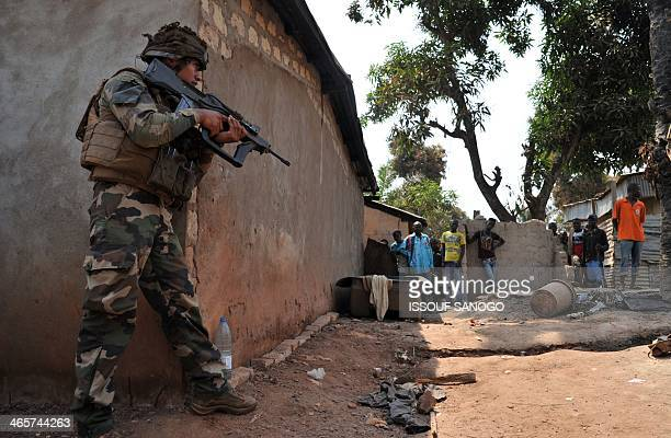 Residents look on as a French soldier of Operation Sangaris patrols in Bangui on January 29, 2014. Gunfire erupted on January 29 in Bangui, still...
