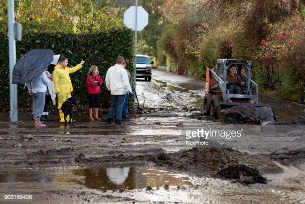 Residents look on as a man clears debris from a mudslide in Los Angeles California on January 9 2018 The deadly storm claimed the lives of 13 people...