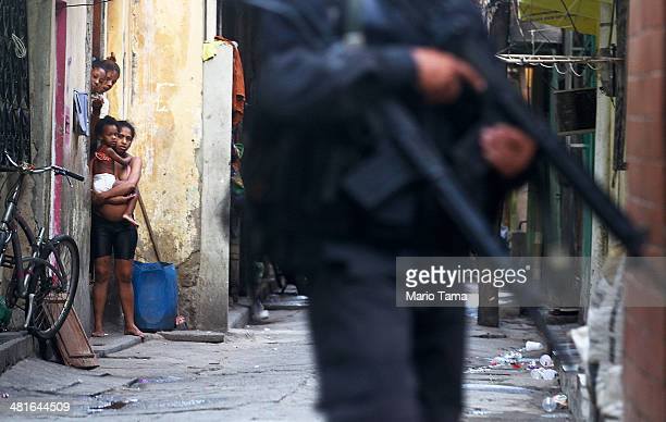 Residents look on as Brazilian military police officers patrol in the unpacified Complexo da Mare one of the largest 'favela' complexes in Rio on...