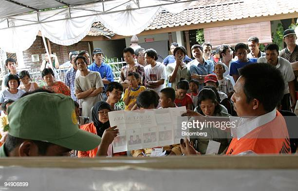 Residents look on as election workers hold up a ballot while counting votes at a small polling station in Jakarta Monday July 5 2004 Indonesians...
