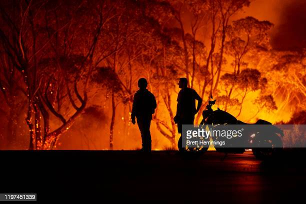 Residents look on as flames burn through bush on January 04 2020 in Lake Tabourie Australia A state of emergency has been declared across NSW with...