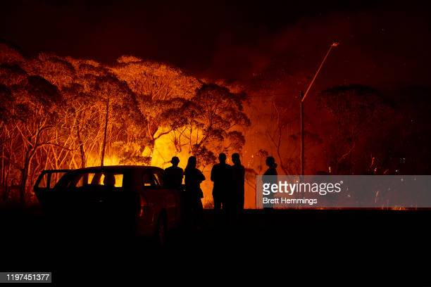 Residents look on as flames burn through bush on January 04, 2020 in Lake Tabourie, Australia. A state of emergency has been declared across NSW with...